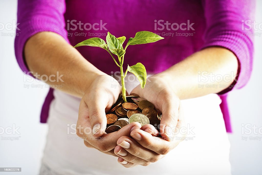Feminine hands hold out seedling surprisingly growing from coins royalty-free stock photo