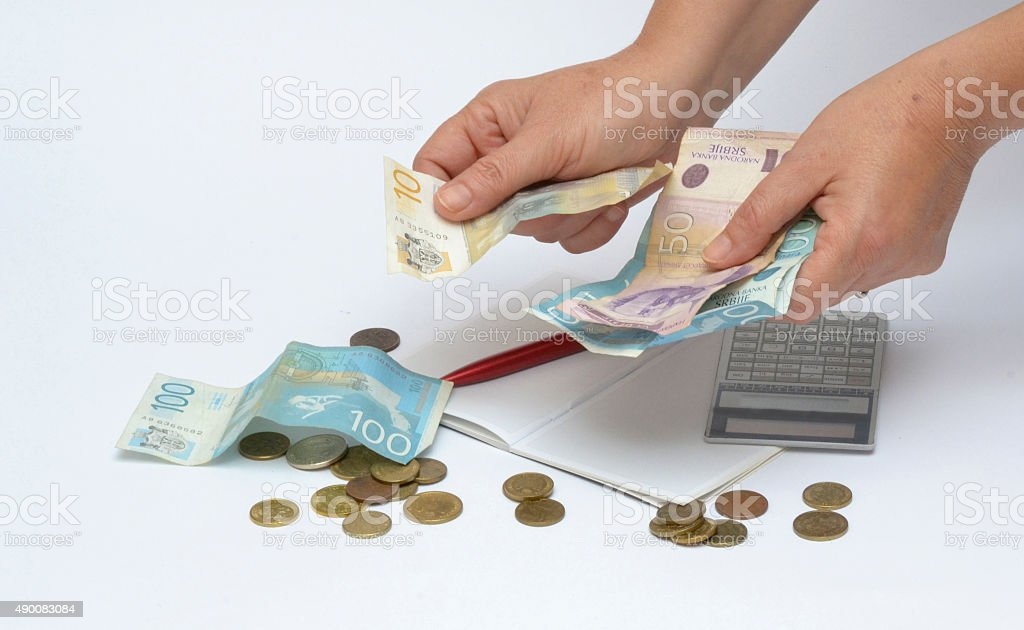 feminine hands money and a calculator stock photo