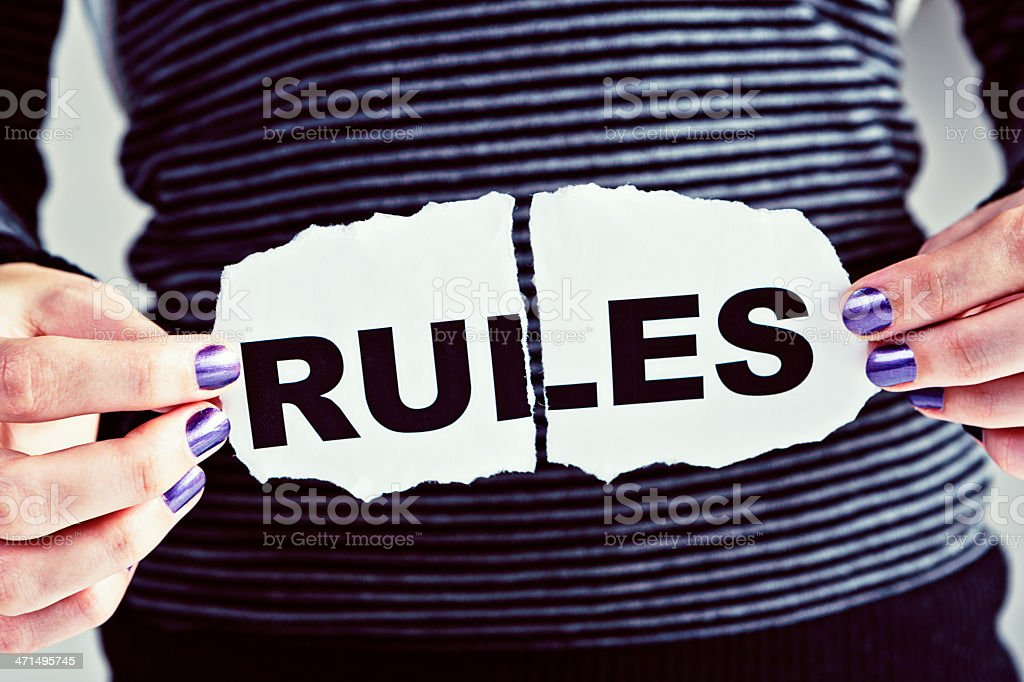 Feminine hands with torn RULES sign royalty-free stock photo