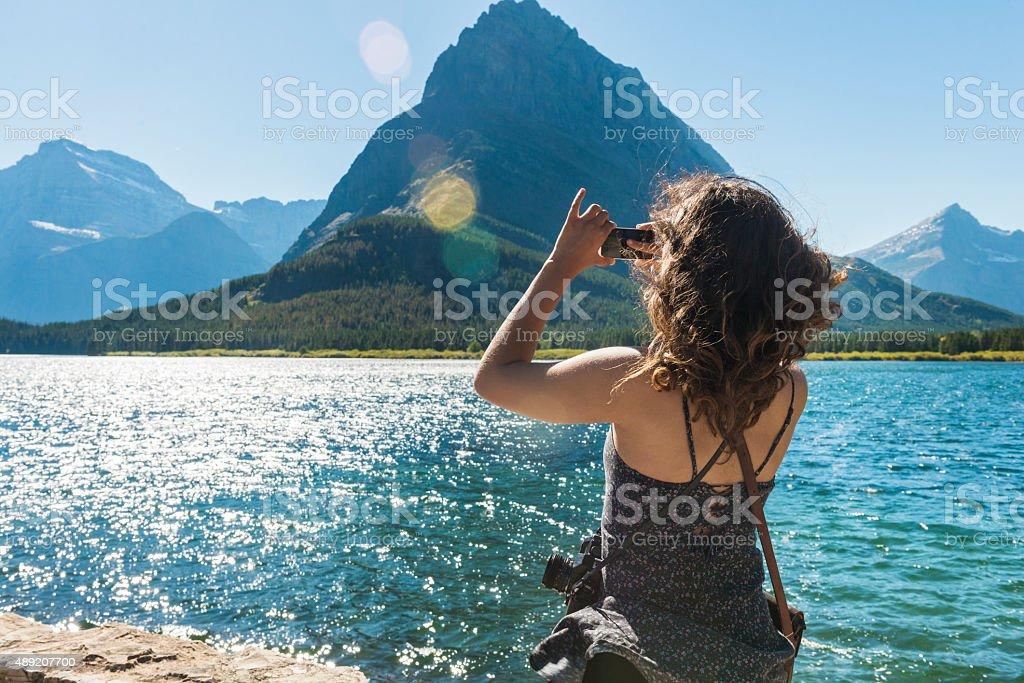 Feminine Woman Explores Scenic Glacier National Park with Camera Montana stock photo