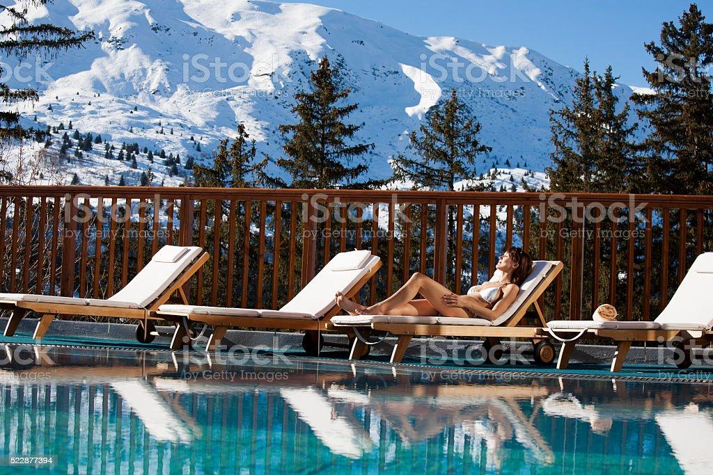 femme au bord d'une piscine à la montagne stock photo