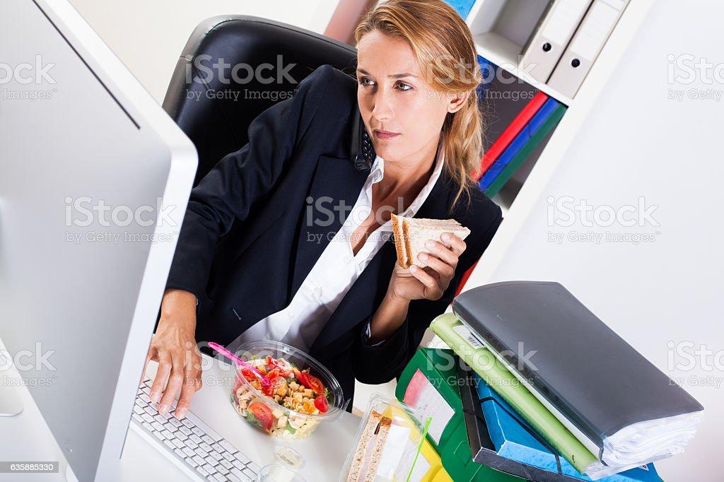 femme qui travaille en mangeant un sandwich stock photo