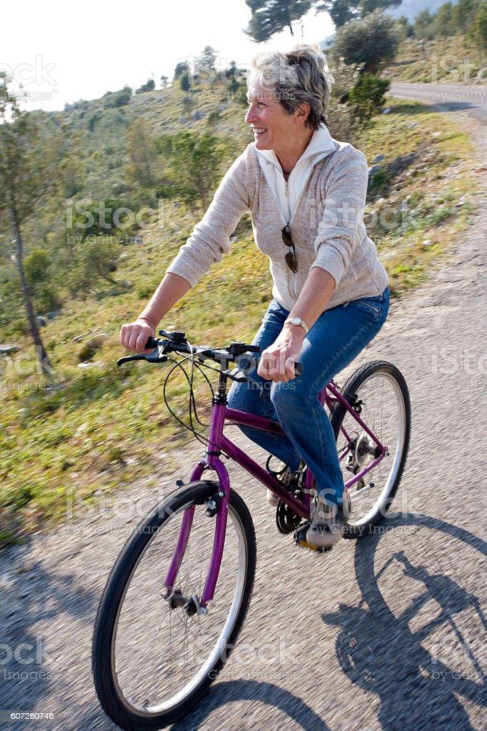femme sénior à vélo stock photo