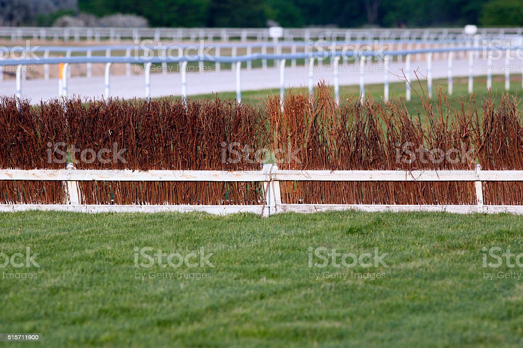 Fence as obstacle for racehorses on race course stock photo
