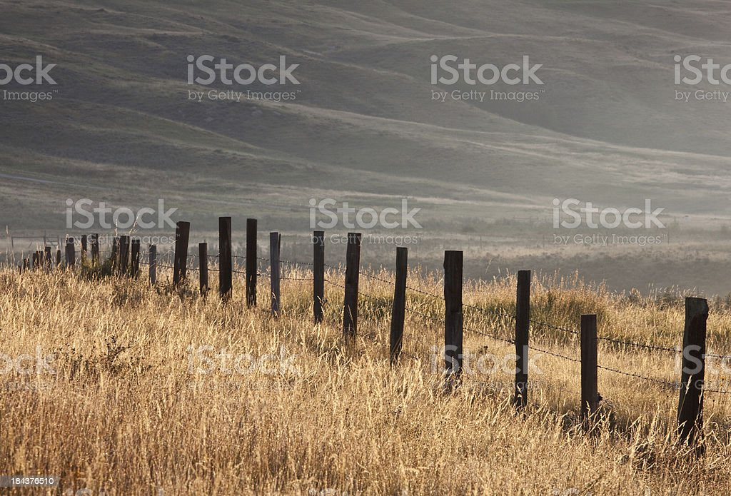Fence Cutting Through Ranchland stock photo