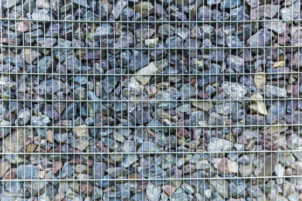 fence from the pieces of granite and metallic grates stock photo
