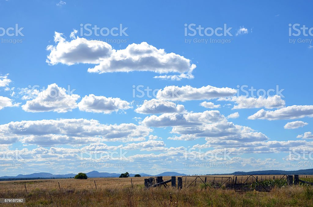 Fence line and gates on farmland under blue skies stock photo