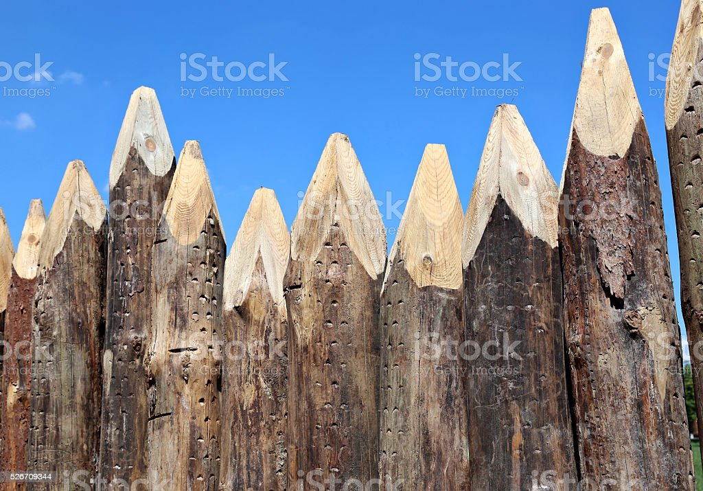 Fence made of sharpened pointed logs stock photo
