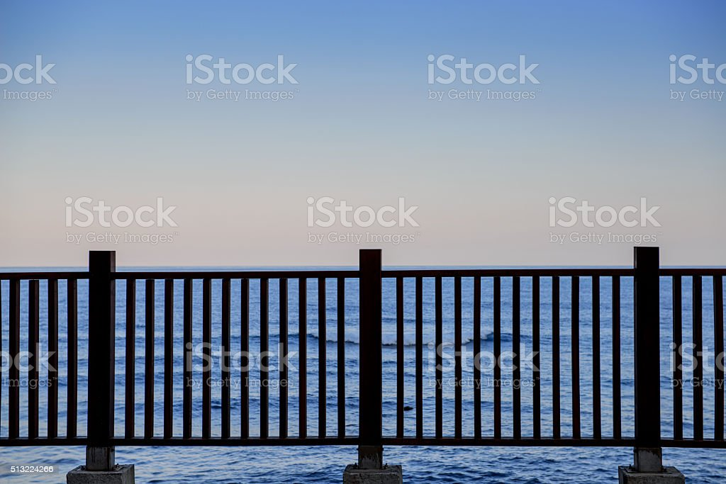 fence on the coast in  sunset stock photo