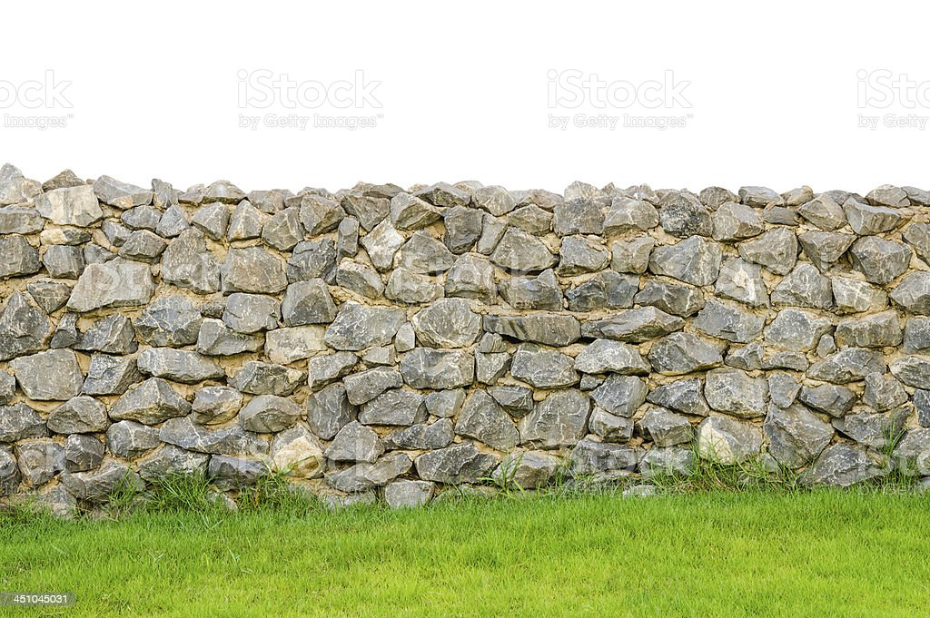 fence real stone wall surface on green grass field stock photo