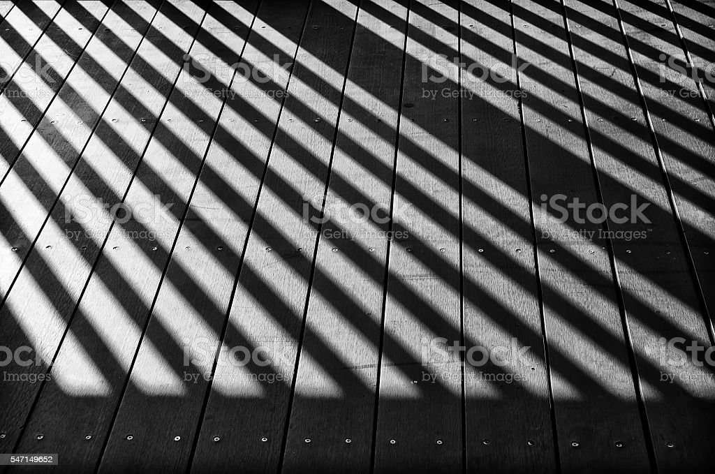 Fence shadow on wooden ground stock photo
