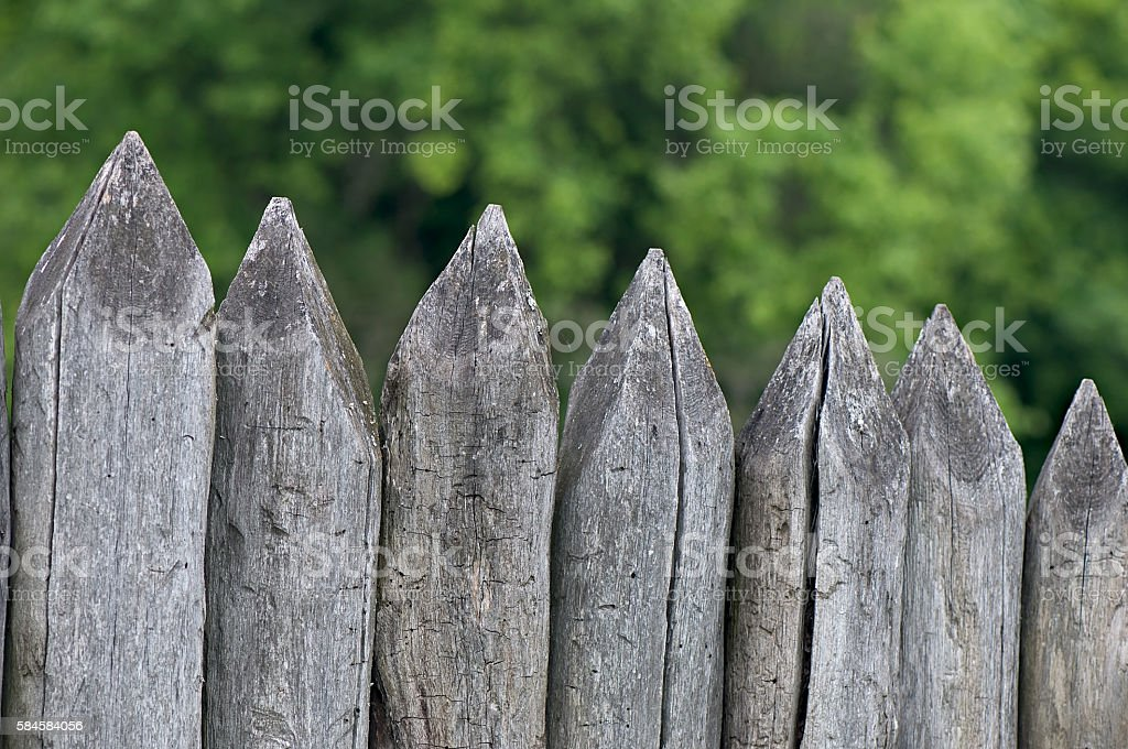 Fence stakes, a fence made of logs, tapered wooden stakes. stock photo