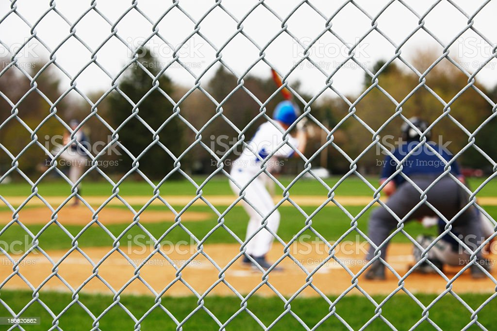 Fence with Baseball Game Pitcher, Batter, Catcher and Umpire stock photo