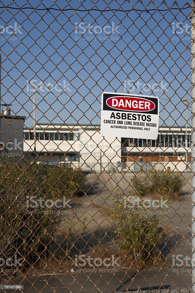 Fence with Danger Asbestos warning sign attached to it. stock photo