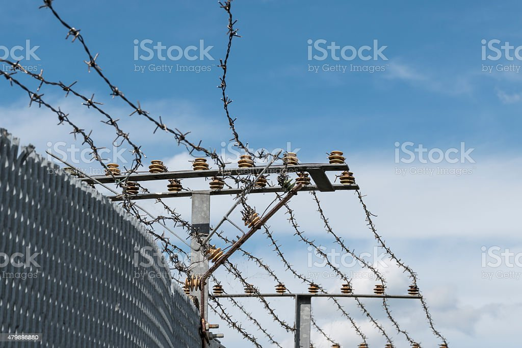 Fence with electric barbed wire stock photo