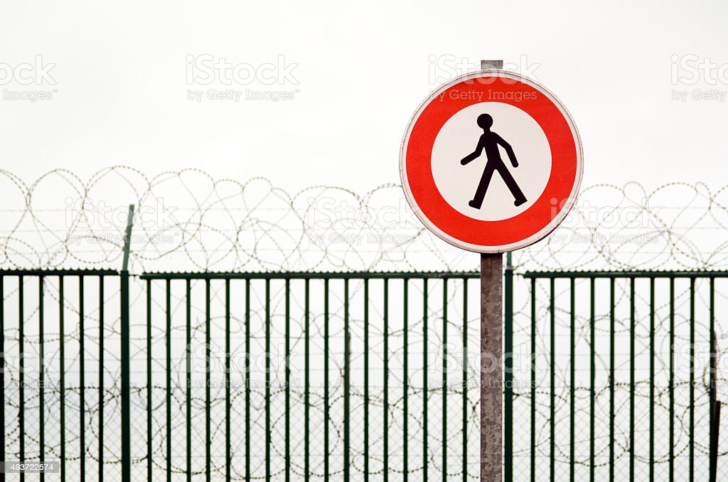 Fence with No Trespassing sign and barbed wire stock photo
