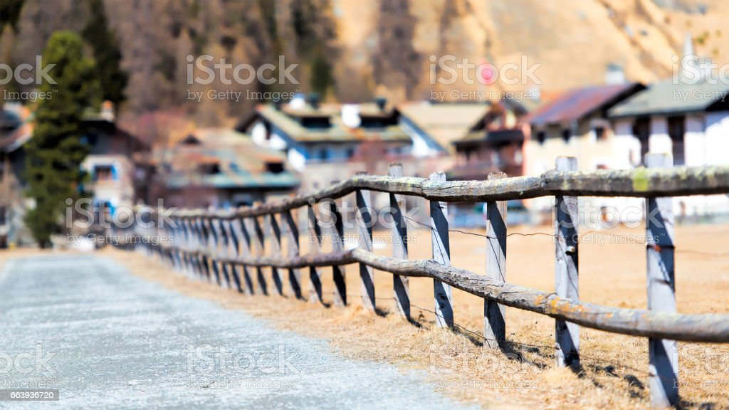 Fence with some typical wooden houses in the background of the village Sils Maria in Switzerland Engadine stock photo