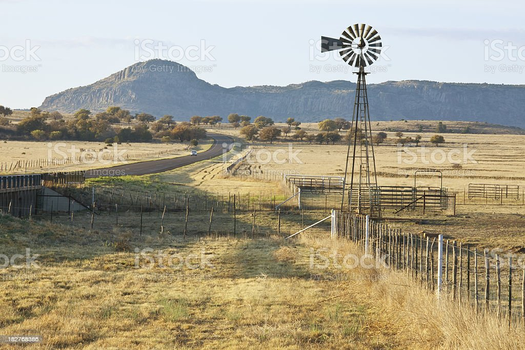 Fence-Line Leading to Ranch Corrals and Windmill stock photo