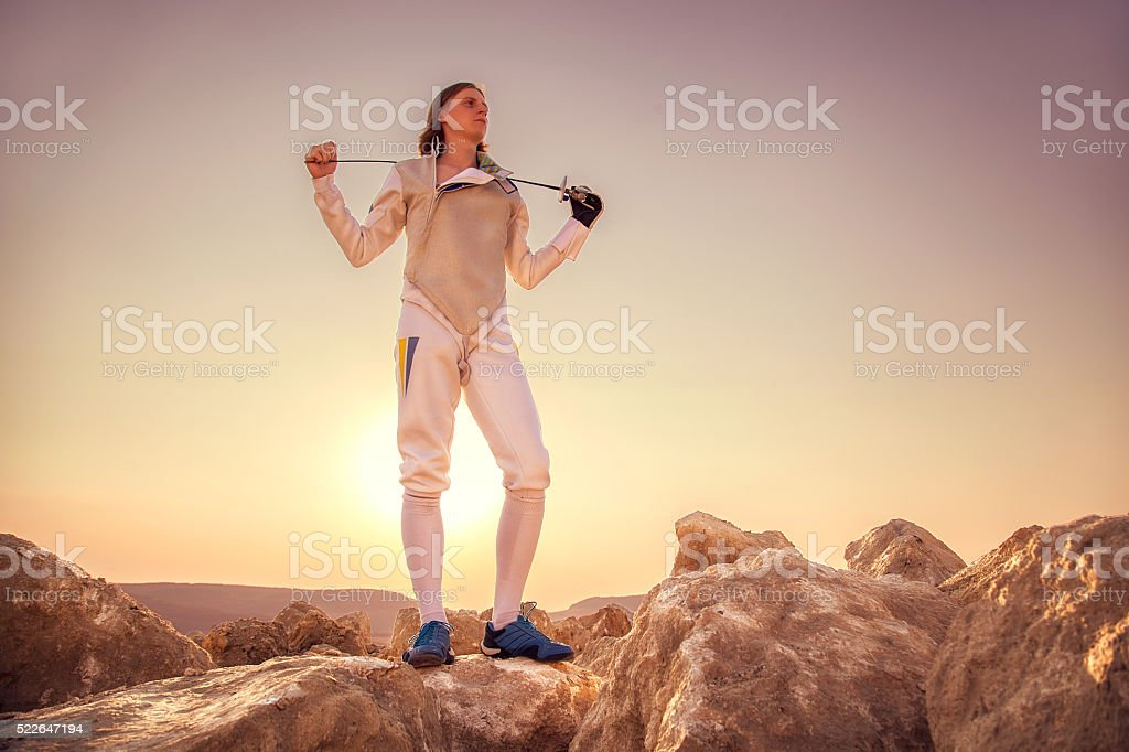 Fencer man holding sword on the shoulders stock photo