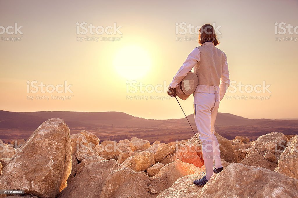 Fencer man holding sword on top of the rock stock photo