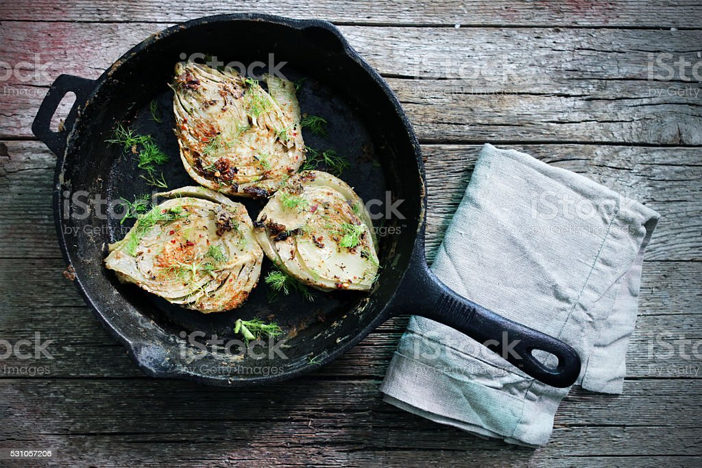Fennel baked in milk, with spices, rustic, italian recipe stock photo