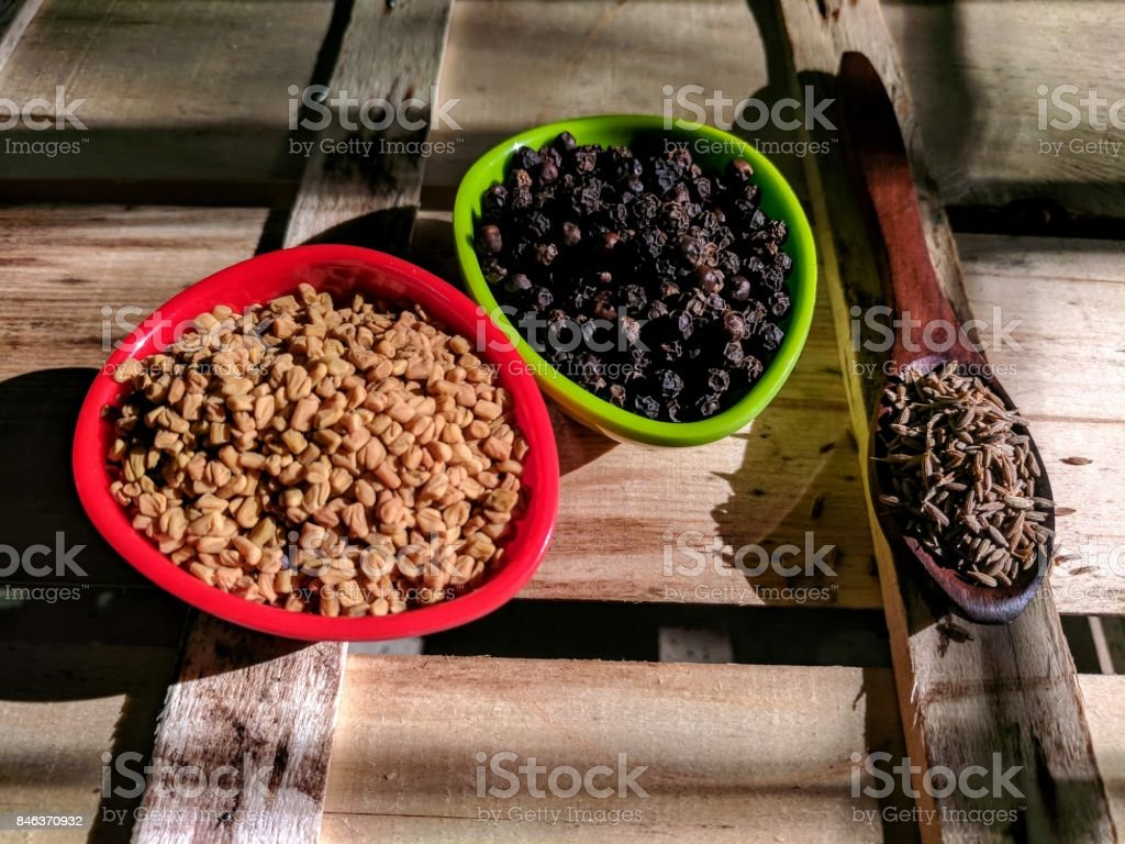 fenugreek, pepper and cumin seeds placed stock photo