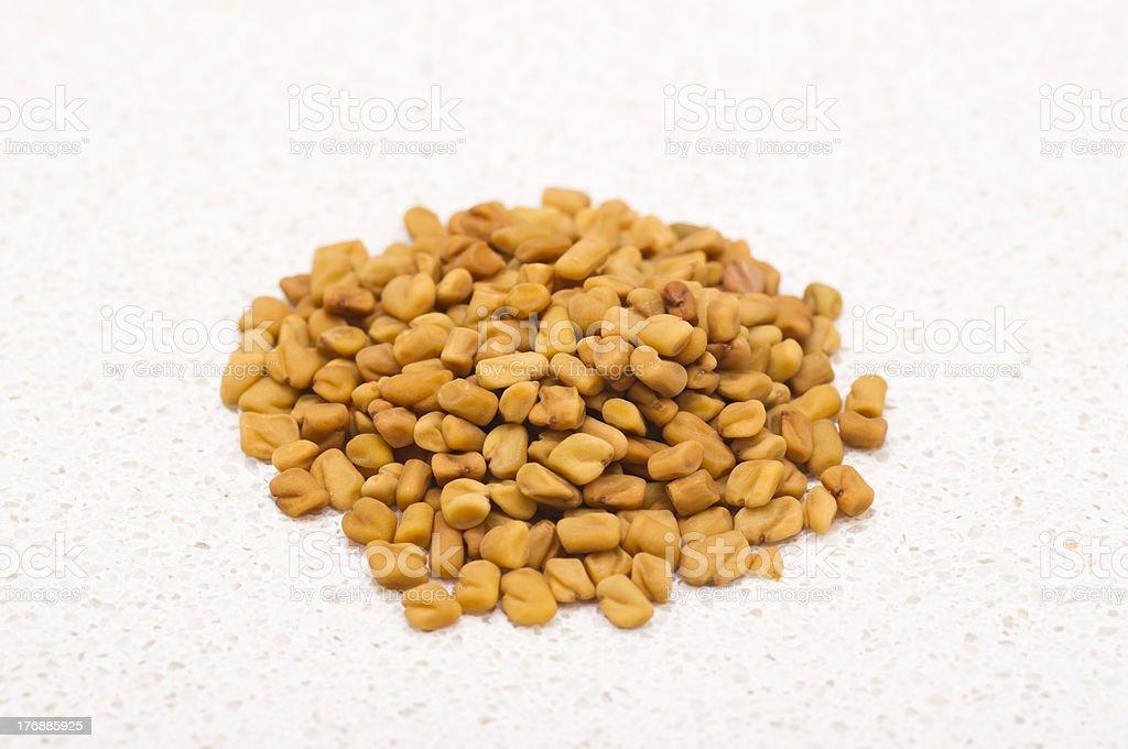 Fenugreek seed on textured kitchen counter top stock photo