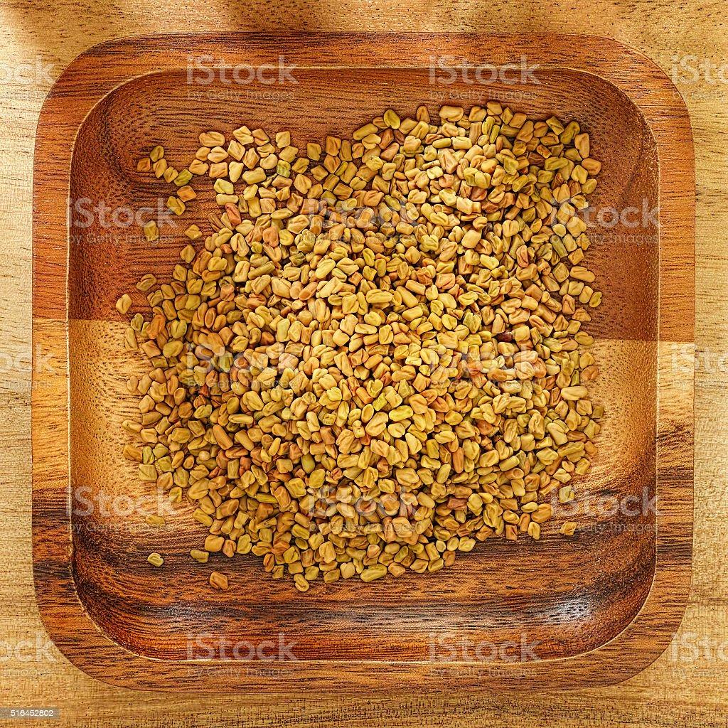 Fenugreek seeds in a wooden tray. stock photo