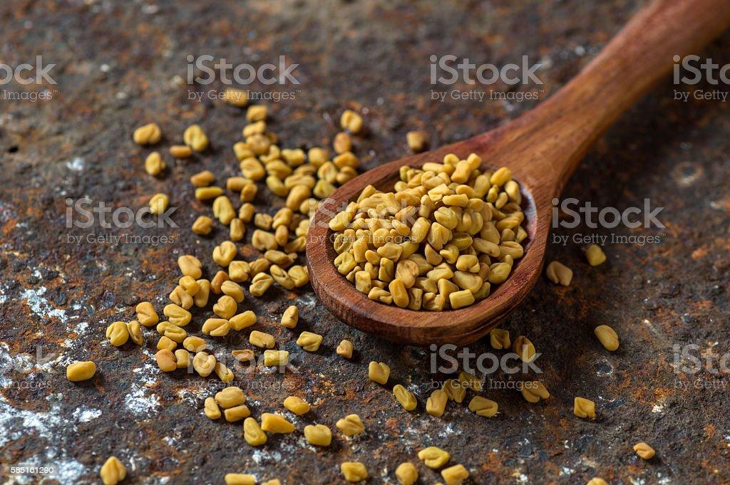 Fenugreek seeds in wooden spoon stock photo