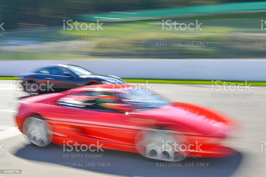 Ferrari F355 and Maserati Quattroporte at high speed stock photo