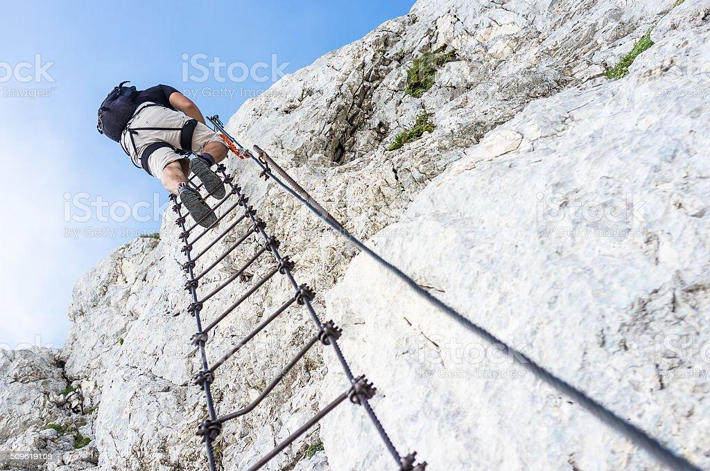 ferrata - crawling man in mountains stock photo