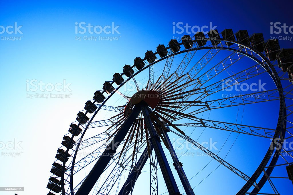 ferris wheel against deep blue sky, back lit royalty-free stock photo