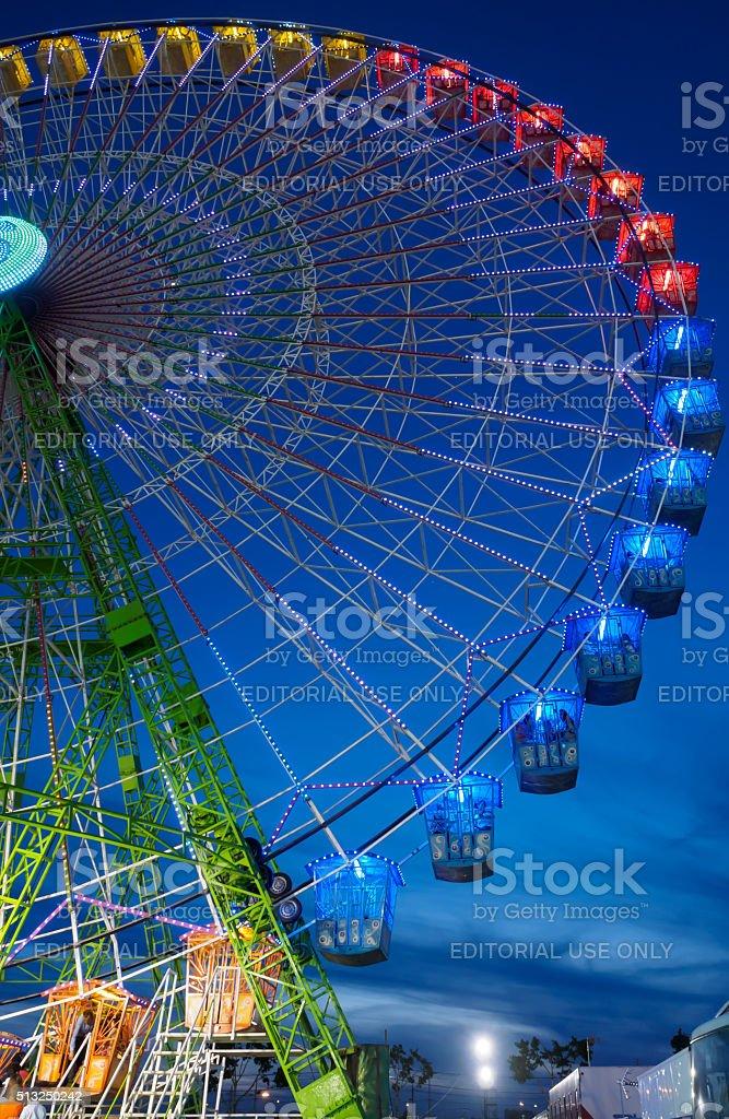 Roda-gigante iluminado à noite na feira de abril em Sevilha foto royalty-free
