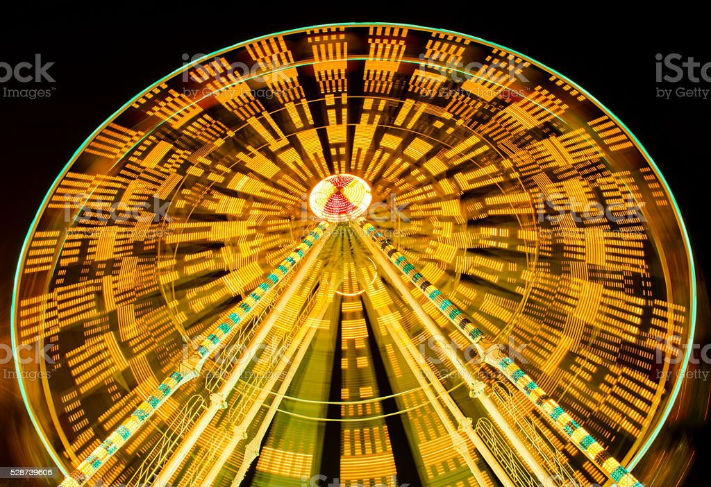 ferris wheel spinning at fairground at night stock photo