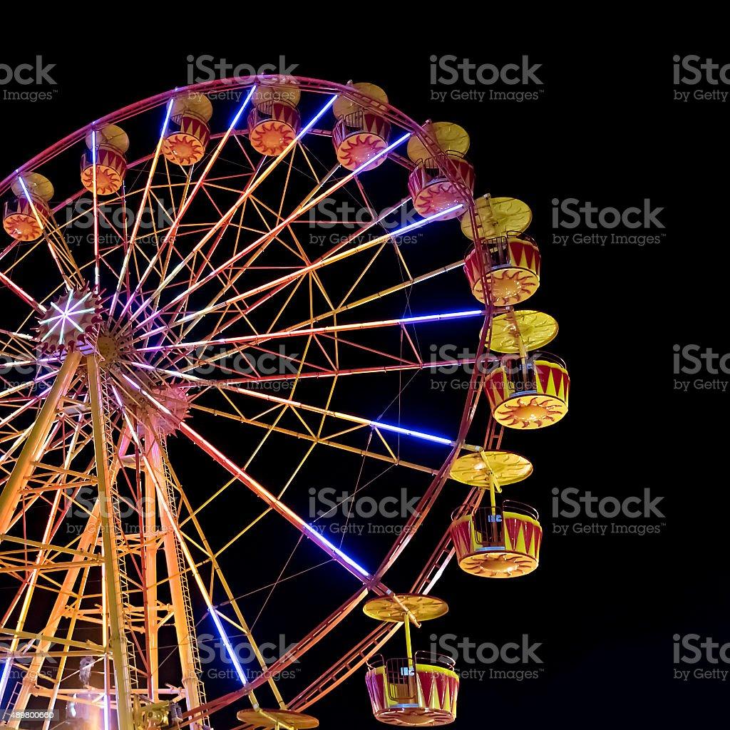Ferris wheel with lights backlighting the night sky stock photo
