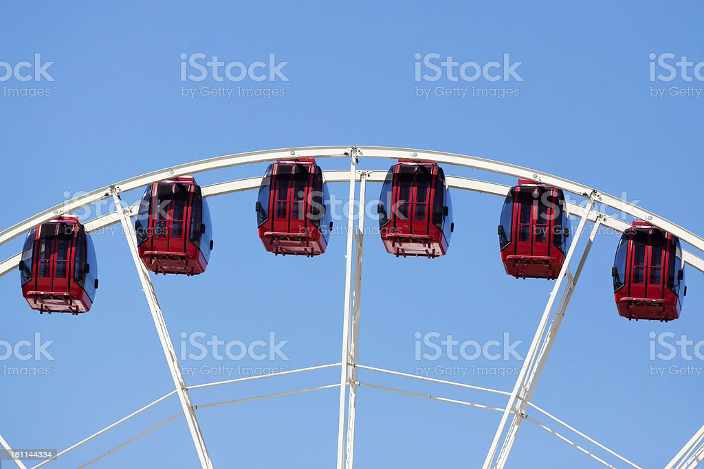 Ferris wheel with red cabins against blue sky, copy space royalty-free stock photo