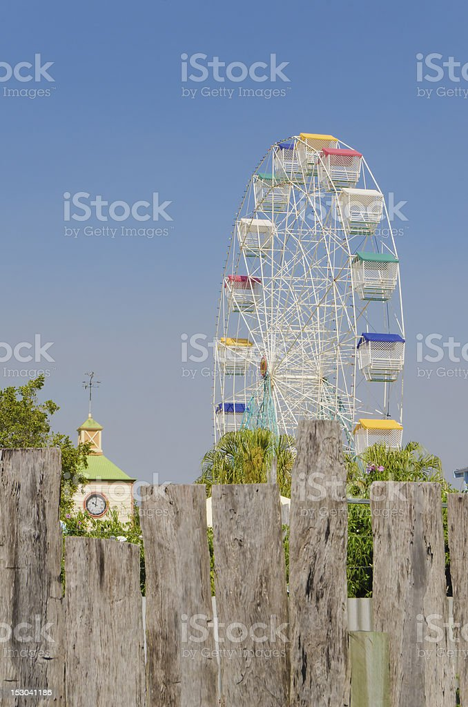 Ferris wheel with wood plank fence in front stock photo