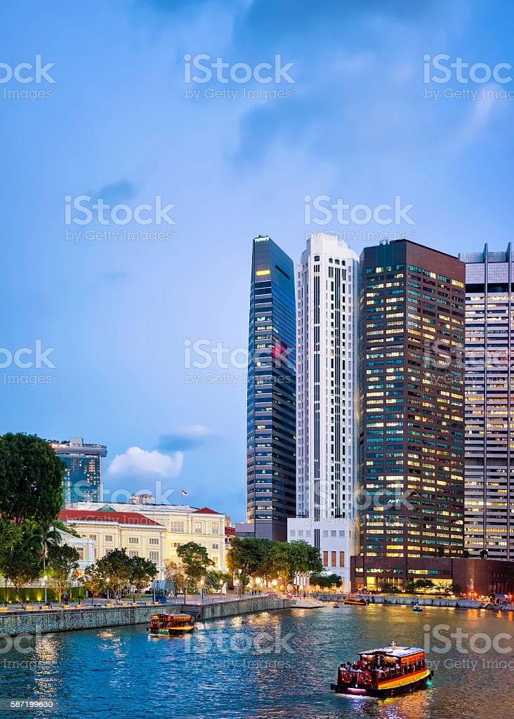 Ferry and Skyscrapers of Financial Center in Singapore at dusk stock photo