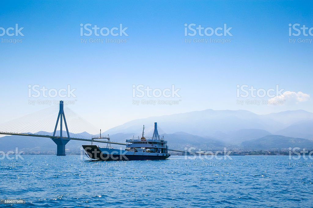 Ferry boat crossing the Corinth Gulf and Antirrio Suspension Bridge. stock photo