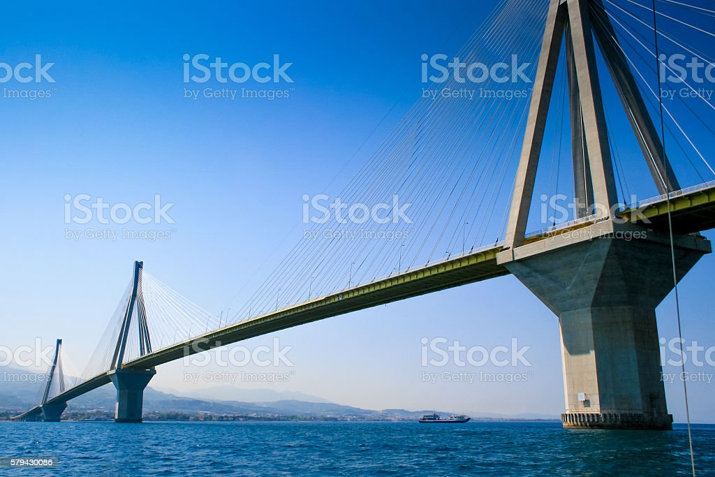 Ferry boat passing Suspension Bridge over the Gulf of Corinth. stock photo