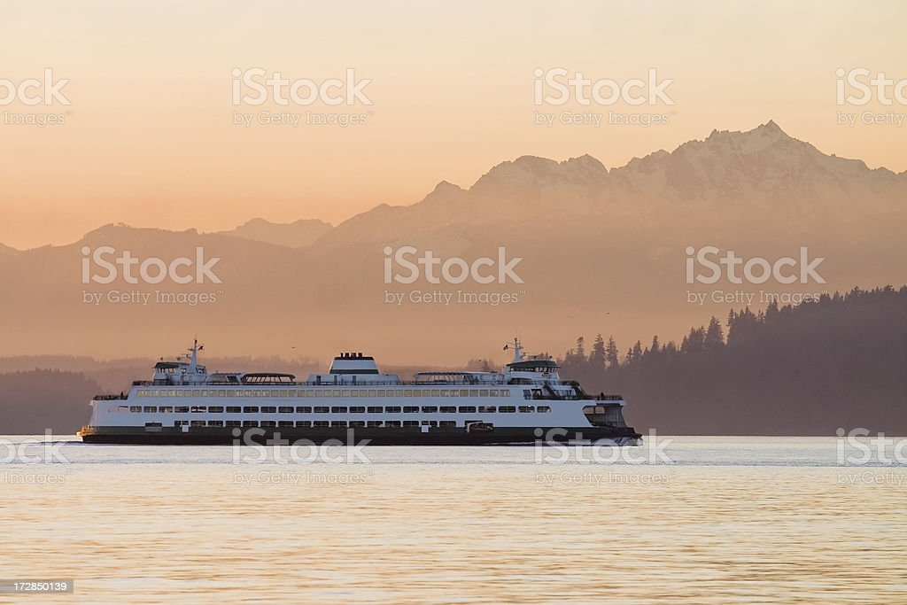 A ferry crossing waters at sunset stock photo