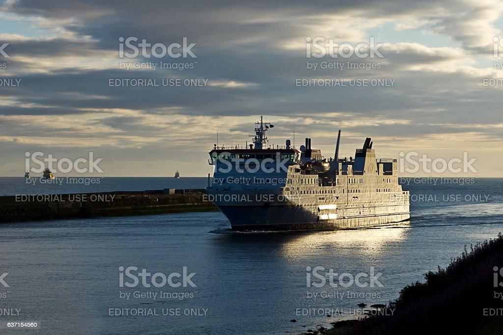 Ferry passes sea wall stock photo