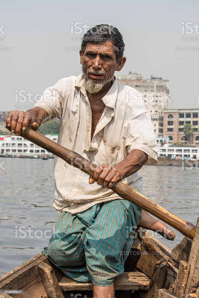 Ferryman rows his boat on river in Dhaka stock photo