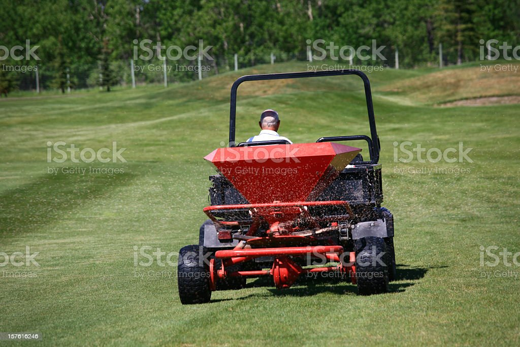 Fertilizing a Golf Course with Spreader stock photo