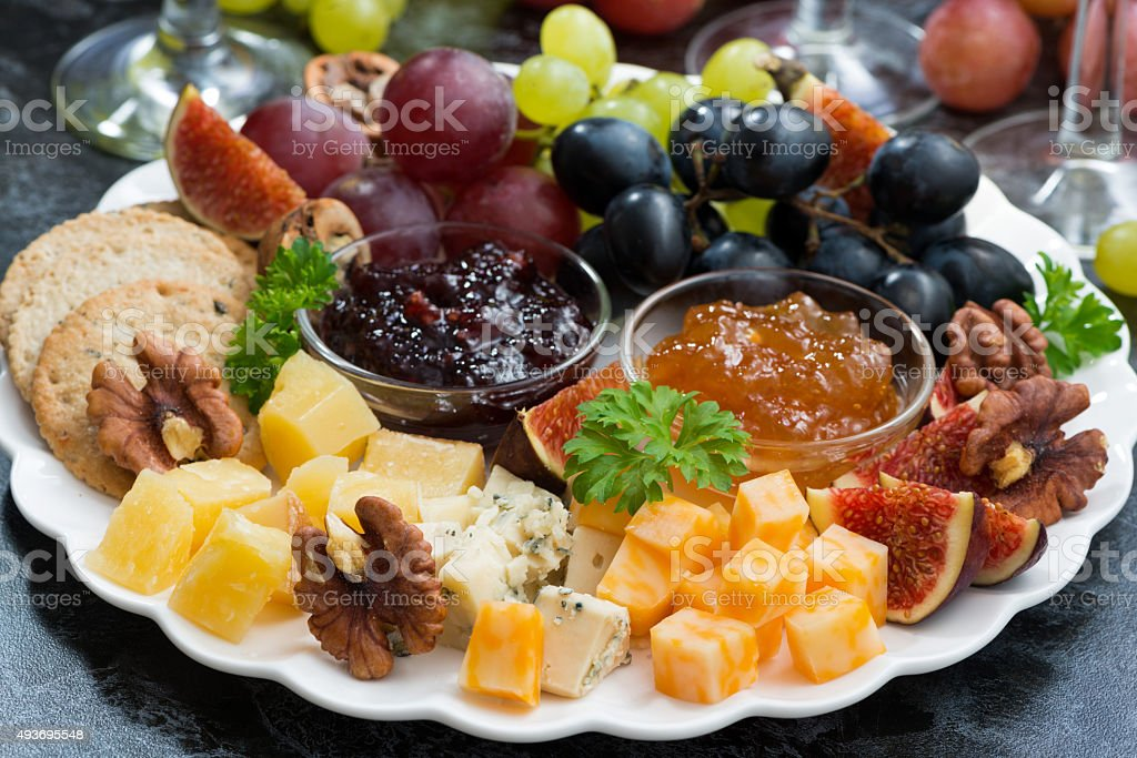 festive appetizers - cheeses, fruits and jams on plate, closeup stock photo