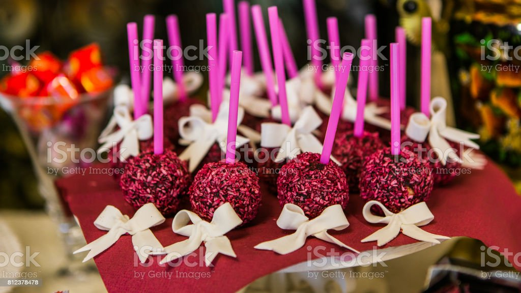 Festive chocolate cake pops with candy sprinkles close-up on the table. horizontal stock photo
