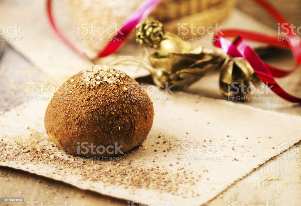 Festive chocolate truffle with red ribbon over wooden background stock photo