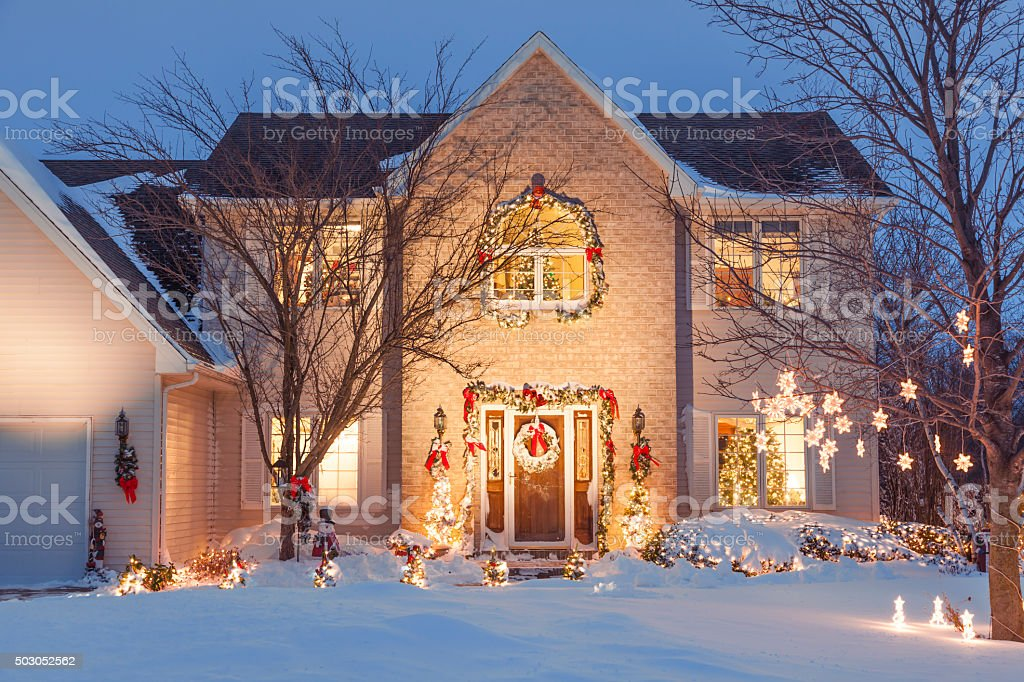Christmas Family Home With Festive Holiday Lighting, covered in snow....