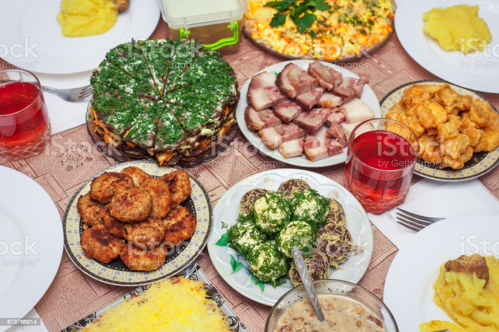 Festive dinner at home, Christmas Day. Bacon, cheese balls, fried fish in batter, cutlets, mushed potato, liver cake, fruit compote in a glass and other. stock photo