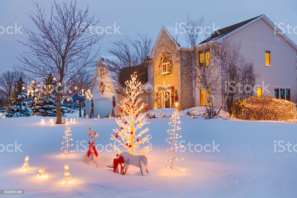 Festive family home with Christmas, holiday decorations, covered in snow stock photo